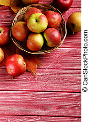 Ripe apples on a red wooden table