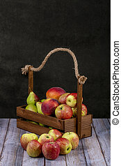 Ripe apples, pears and peaches in a wooden box