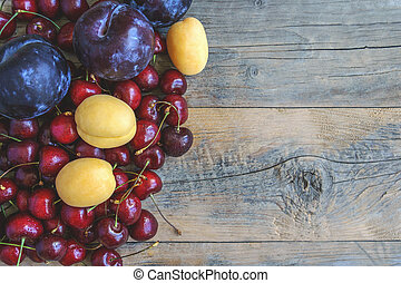 Ripe apricot cherry fruit and plum on a beautiful wooden background. Copy space. The concept of healthy eating