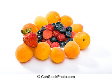 Ripe apricots and berries of strawberry, raspberry and bilberry on white background