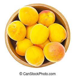 ripe apricots in wooden bowl isolated on white background