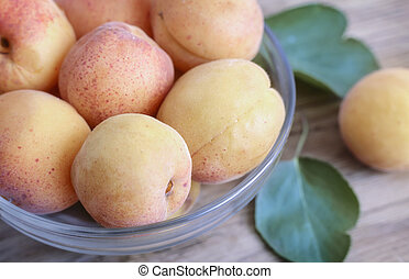 Ripe apricots on the table in a glass vase.