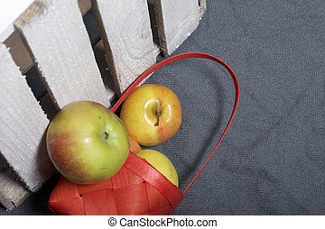 Ripe aromatic apples from a wicker basket on a gray cloth. Nearby is a wooden box, knocked out of the boards.