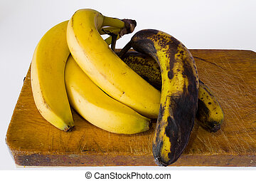 ripe banana and rot banana over the wood table