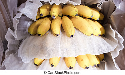Ripe bananas in a box in a store. At the display window.