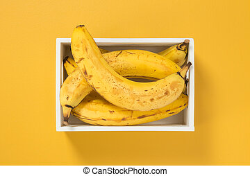 Ripe bananas in a box on bright yellow background