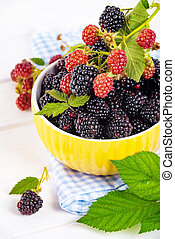 Ripe blackberries with leaves in a yellow modern bowl on a wooden board on a light background