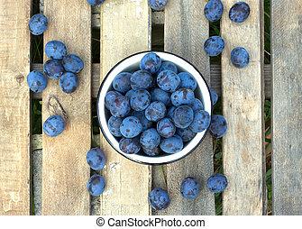 Ripe blue plums in metal bowl close