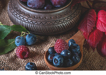 Ripe blueberries and raspberries lie in a handmade ceramic ...