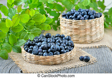 Ripe blueberries in basket on wooden table