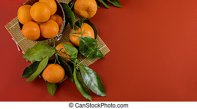 Ripe bright raw tangerines on branch with green leaves in a bowl on red background.