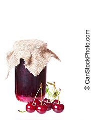 ripe cherries and a glass jar with cherry jam