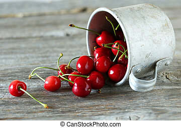Ripe cherries in cup on grey wooden background
