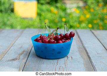 Ripe cherries in the blue bowl on wood background.