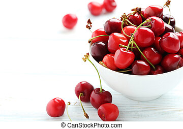 Ripe cherries on a white wooden table