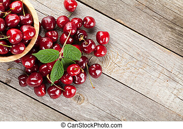 Ripe cherries on wooden table. View from above with copy...