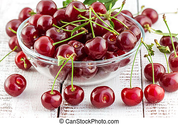 cherries with leaves in a bowl on a white wooden background