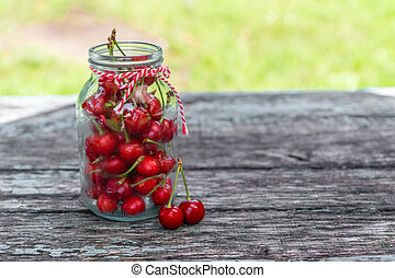 Ripe cherry berry in glass bottle on a wooden background