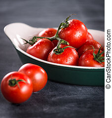 Ripe cherry tomatoes in a bowl on a black background
