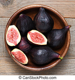 Ripe figs in wooden bowl close-up