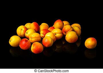 Ripe fresh apricots isolated on black background.