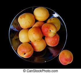 Ripe fresh apricots isolated on black background