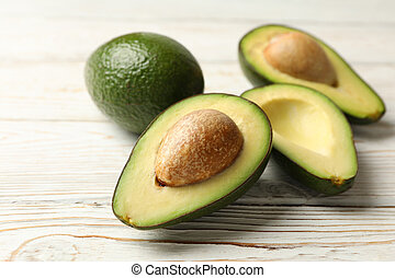 Ripe fresh avocado on white wooden background, close up