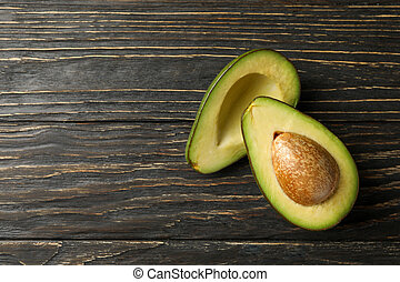 Ripe fresh avocado on wooden background, top view
