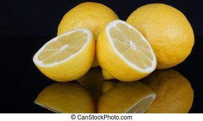 Ripe fresh juicy yellow lemon on black background rotate -...