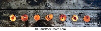 Ripe fresh peaches, whole, cut and broken into halves, laid out in a row on a wooden background, a banner.