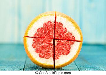 ripe fresh sliced grapefruit on a blue wooden background. ...