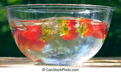 Ripe fresh strawberries floats at the water at bowl on...