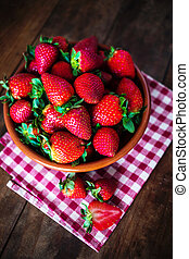 Ripe Fresh strawberries in a bowl on dark wooden table with copy space