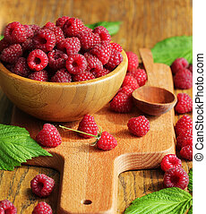 Ripe fresh sweet raspberries in a wooden bowl on wooden table background