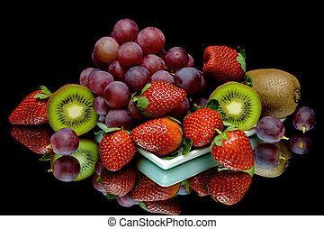 grapes, kiwi and strawberries on a black background