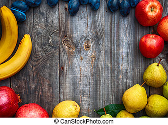 Ripe fruits lined frame on a gray wooden surface