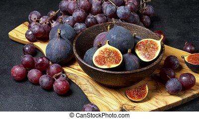 Ripe Grapes and Figs on dark concrete background - Ripe...