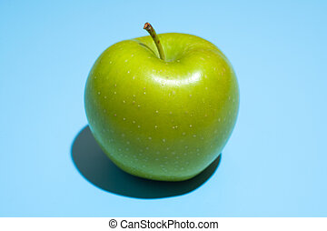 Ripe green apple on blue background. Healthy eating and dieting concept