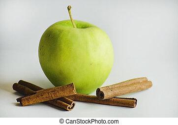Ripe green apple with cinnamon sticks