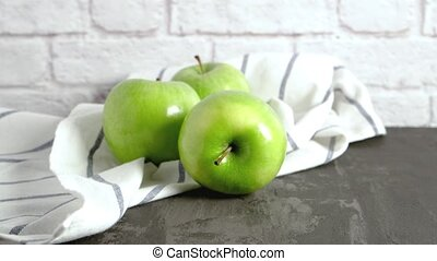 Ripe green apples and napkin on kitchen counter top.