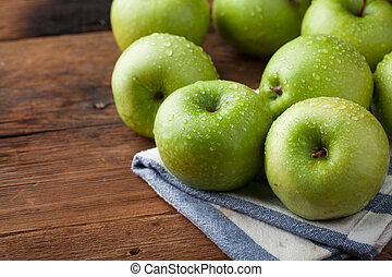 Ripe green apples in a wooden bowl on an old rustic table. Useful fruits on wooden background. with copy space