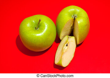 Ripe green cut apple Isolated on a red background. Healthy eating and dieting concept