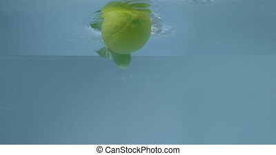 Ripe green lime pours into the water with air bubbles. - ...