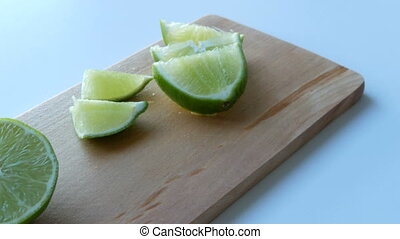 Ripe green lime sliced on kitchen wooden board on a white table background