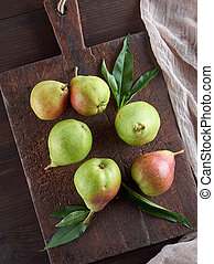 ripe green pears on a brown wooden board