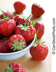 Ripe Juicy Strawberries in the White Bowl on the Wooden Table