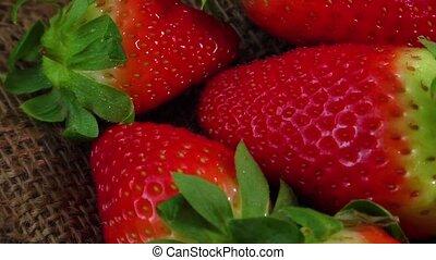Ripe juicy strawberries on jute sackcloth