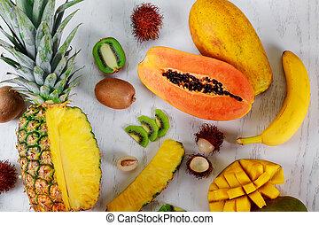 Ripe juicy tropical summer seasonal fruits mango papaya pineapple kiwi bananas wood background lifestyle super foods