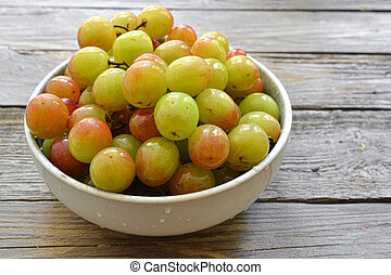 Ripe large grapes. Grapes in a plate isolated on a wooden background. Free space for text.