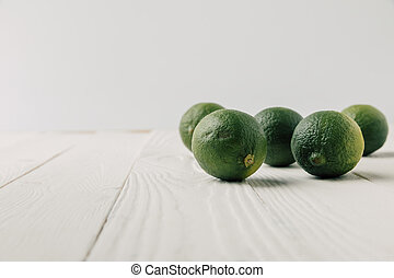 Ripe limes on white wooden background